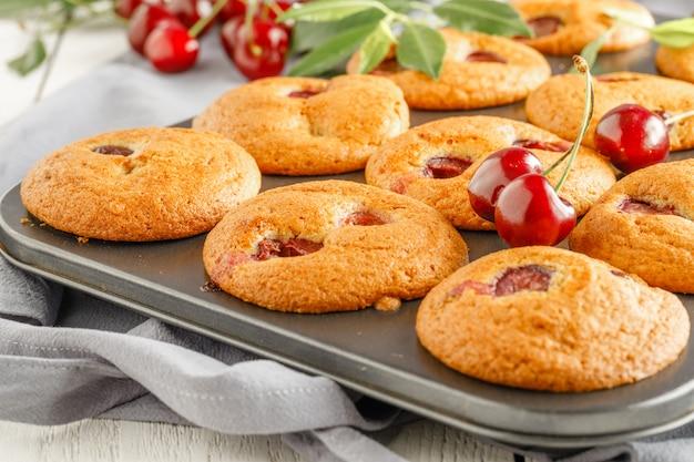 Muffins de cereja caseiros e cerejas frescas sobre um fundo claro