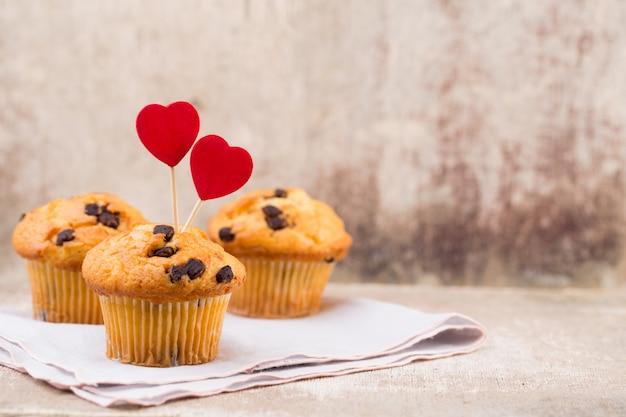 Muffins de chocolate caseiros com coração, fundo vintage.