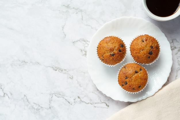 Muffins de chocolate colocados em um prato redondo branco com uma xícara de café
