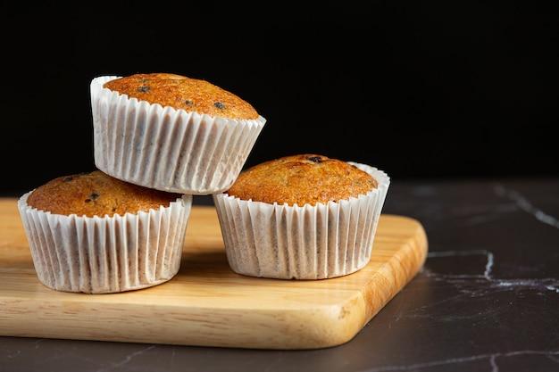 Muffins de chocolate colocados em uma tábua de madeira