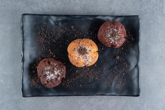 Muffins de chocolate com bolinhos de nozes em um tabuleiro escuro