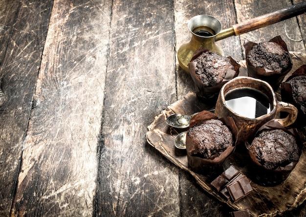 Muffins de chocolate com café quente. em uma mesa de madeira.