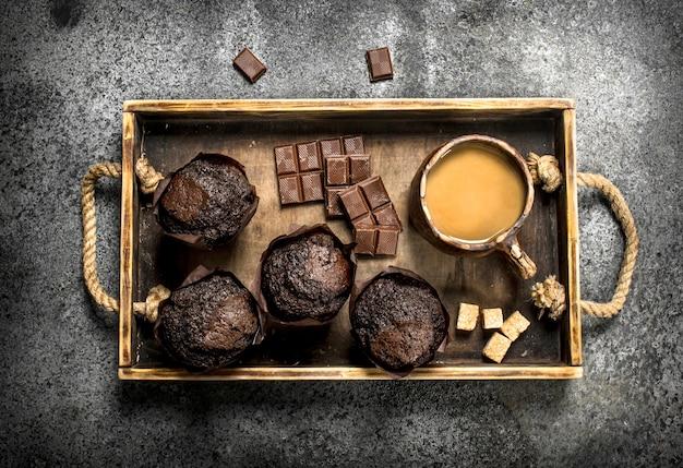 Muffins de chocolate com café. sobre uma mesa rústica.