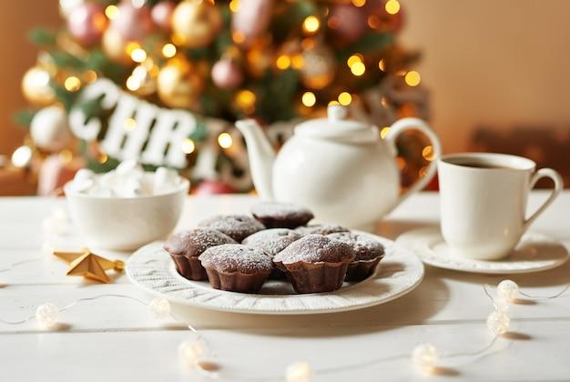 Muffins de chocolate com chá de árvore de natal. natal. modelo de cartão e calendário. decoração de natal. jantar de férias, doces para as crianças.