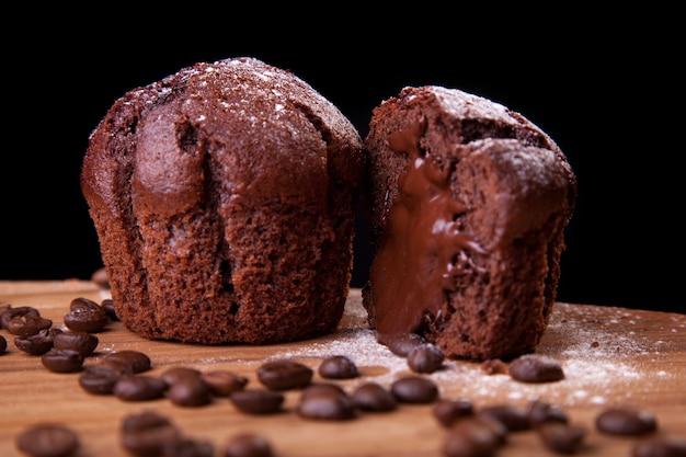 Muffins de chocolate com chocolate e grãos de café e açúcar em uma mesa de madeira e fundo preto.