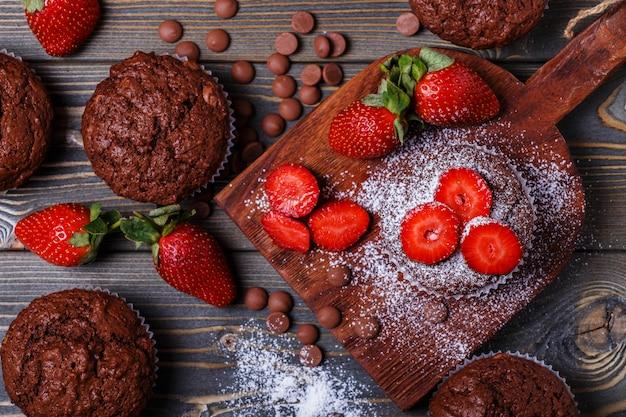 Muffins de chocolate com morango no escuro.