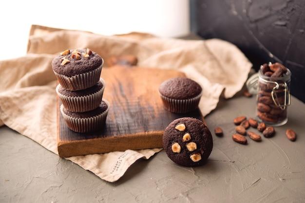 Muffins de chocolate com nozes em uma mesa de madeira. deliciosa sobremesa doce. estilo rústico.