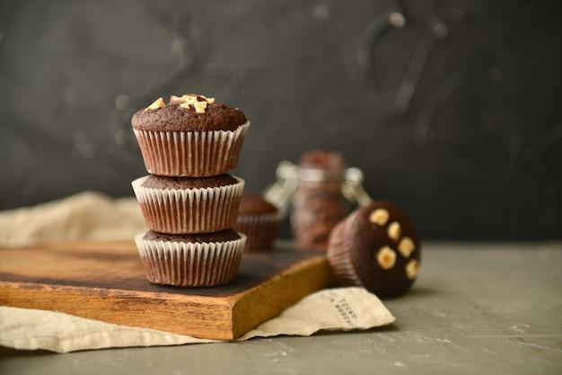 Muffins de chocolate com nozes em uma mesa de madeira muffins caseiros com nozes e grãos de café