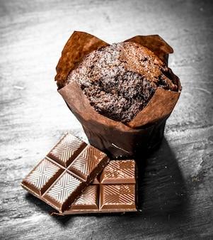 Muffins de chocolate com pedaços de chocolate. no quadro negro.