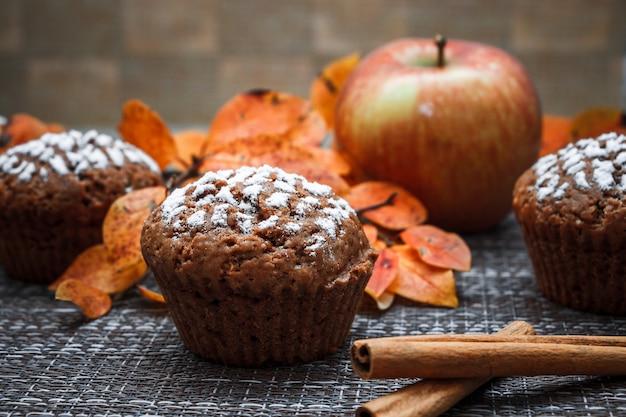 Muffins de chocolate com recheio de maçã em um fundo de folhas de outono e canela