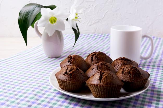 Muffins de chocolate e caneca de café no guardanapo xadrez