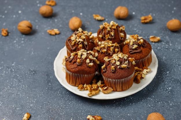 Muffins de chocolate e nozes com uma xícara de café com nozes na superfície escura