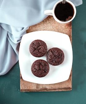 Muffins de chocolate e uma xícara de café em um pedaço de madeira.