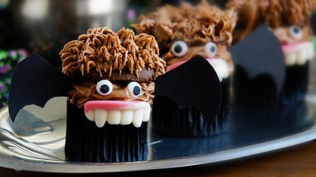 Muffins de chocolate em forma de morcegos-vampiros. para festa de halloween