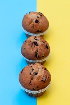 Muffins de chocolate em fundo azul e amarelo