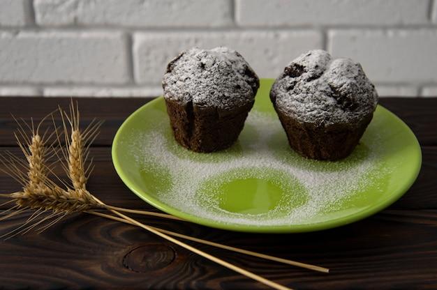 Muffins de chocolate em um prato verde sobre uma superfície de madeira