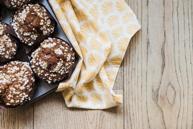 Muffins de chocolate na bandeja perto do guardanapo em pano de fundo de madeira