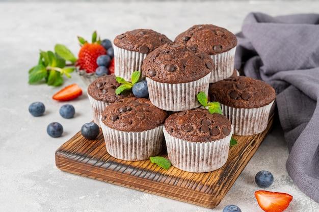 Muffins de chocolate ou cupcakes com gotas de chocolate em uma placa de madeira sobre um fundo cinza com frutas frescas e hortelã. copie o espaço.
