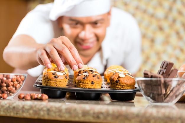 Muffins de cozimento do homem asiático na cozinha de casa