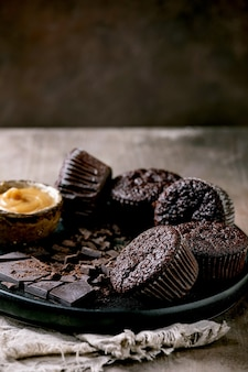 Muffins de cupcakes de chocolate caseiros com calda de caramelo salgado e chocolate escuro picado na placa de cerâmica preta sobre a mesa de textura de concreto.