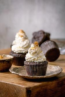Muffins de cupcakes de chocolate caseiros com creme de manteiga batida branca e caramelo salgado na placa de cerâmica na mesa de madeira.