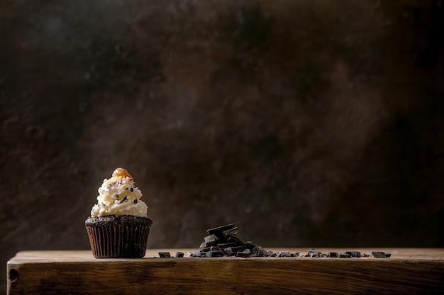 Muffins de cupcakes de chocolate caseiros com creme de manteiga chantilly branca e caramelo salgado no prato de cerâmica, servido com chocolate escuro picado na mesa de madeira. copie o espaço