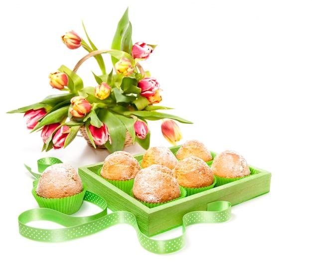 Muffins de limão e tulipas isoladas no branco