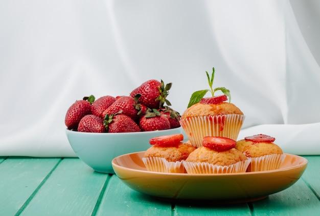 Muffins de morango vista frontal em um prato com morangos em uma tigela