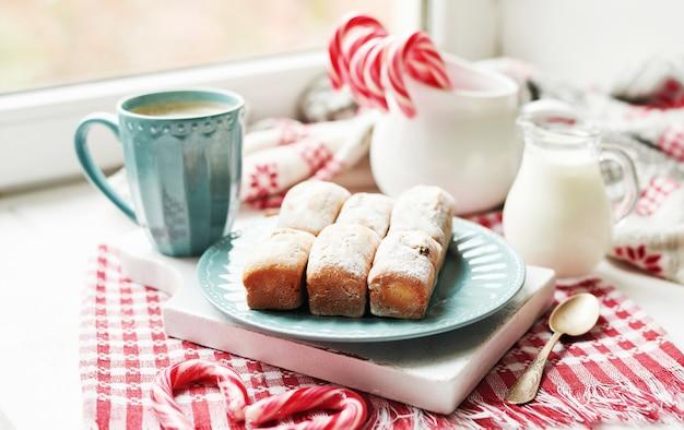 Muffins de natal, leite, cacau, marshmallows, pirulitos de doces no prato perto da janela
