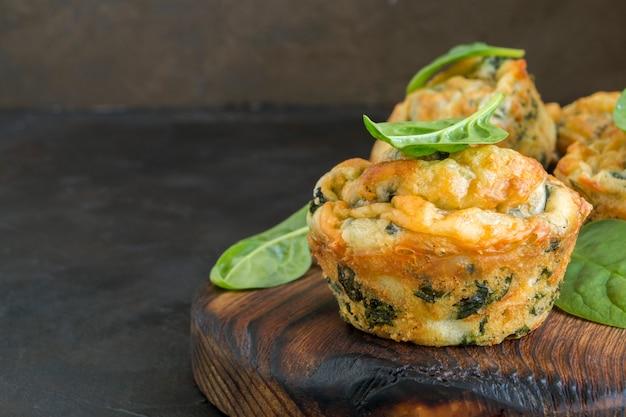 Muffins de queijo caseiro com espinafre. em fundo escuro.