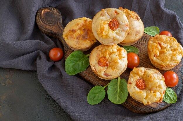 Muffins de queijo caseiro em um fundo escuro.