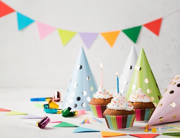 Muffins de vidro com velas e chapéus de festa