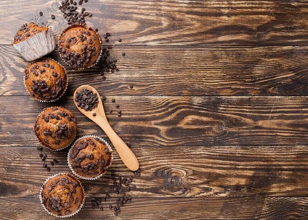 Muffins de vista superior deliciosa com colher cheia de pepitas de chocolate