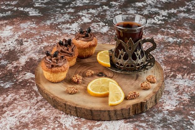 Muffins e um copo de chá em uma placa de madeira.