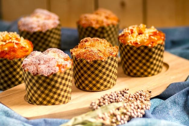 Muffins em prato de madeira e mesa com fundo de madeira