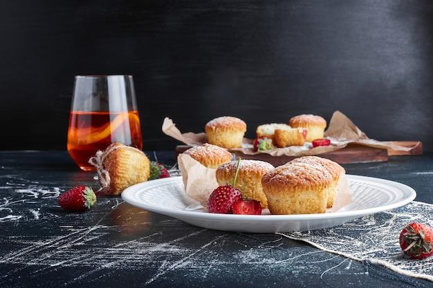 Muffins em um prato branco com frutas ao redor.
