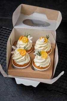 Muffins festivos com creme de cream cheese e recheio de frutas cítricas. confeitaria para o feriado. sobremesa decorada com flocos de neve de kumquat, alecrim e mástique, embalada em caixa oferta.