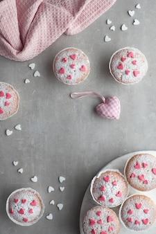 Muffins polvilhados de açúcar com corações de glacê de fondant rosa e branco