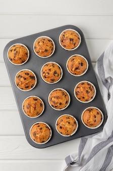 Muffins prontos com gotas de chocolate assados em um fundo branco de madeira. receita passo a passo