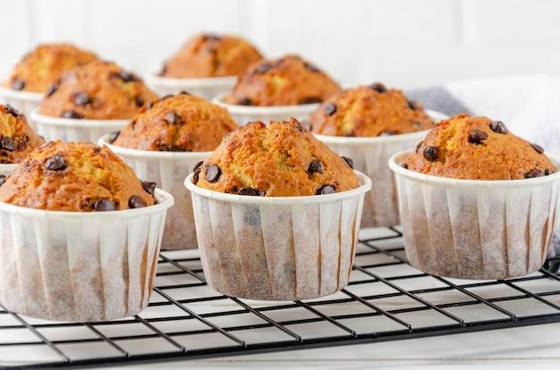 Muffins prontos com gotas de chocolate em um fundo branco de madeira
