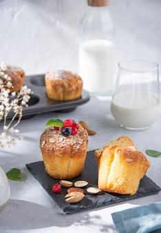 Muffins recém-assados com frutas vermelhas em uma mesa branca com um copo de leite