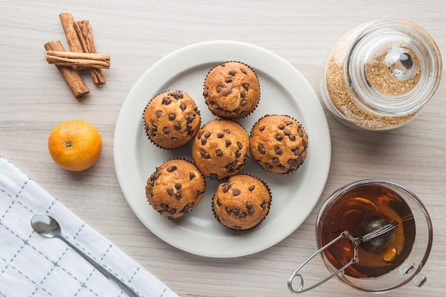 Muffins, xícara de chá, açúcar, tangerina e canela