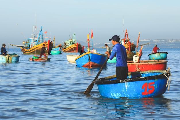 Mui ne vietnam, 22 de janeiro de 2019: pescadores em uma linha de barcos tradicionais vietnamitas na vila de pescadores em mui ne, vietnã.