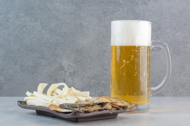 Muita comida deliciosa para a cerveja em pratos pretos.