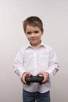 Muita diversão. menino alegre e feliz jogando videogame enquanto se diverte