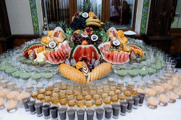 Muita variedade de frutas e bebidas servidas em uma mesa de comemoração