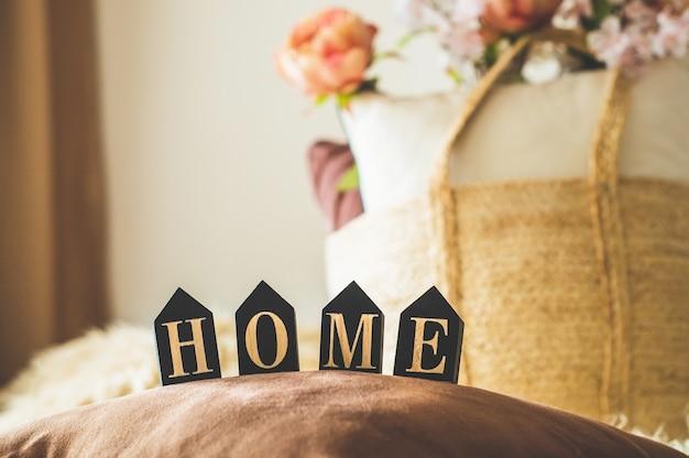 Muitas almofadas decorativas aconchegantes e a inscrição casa. no interior da casa na cama com uma cesta de vime e flores nela. primavera no interior da casa. conceito de casa