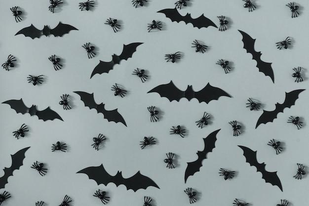 Muitas aranhas pretas decorativas e morcegos são dispostos na superfície cinza.