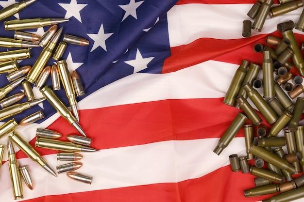 Muitas balas e cartuchos amarelos de 9 mm e 5,56 mm na bandeira dos estados unidos. conceito de tráfico de armas em território dos eua ou objetos de campo de tiro