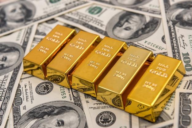 Muitas barras de ouro na superfície das notas de dólar